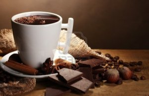 12020834-cup-of-hot-chocolate-cinnamon-sticks-nuts-and-chocolate-on-wooden-table-on-brown-background